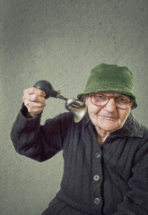 Elderly woman squeezing horn into her own ear.