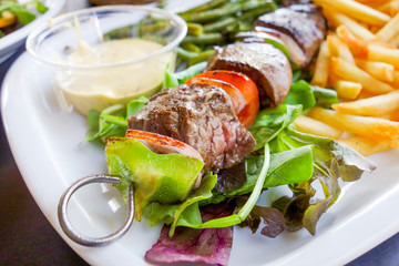 Grilled skewers - Grilled meat ribs on the plate with hot sauce
