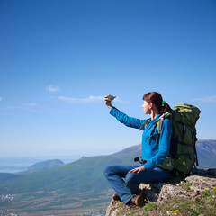 Woman with backpack take a picture of herself on top of mountain