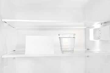 Wasserglas mit leerem Zettel im Kühlschrank
