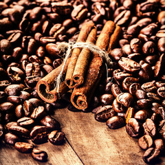 Roasted Coffee beans and cinnamon sticks on grunge wooden backgr
