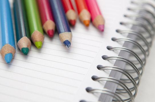 crayons de couleurs sur carnet a spirales
