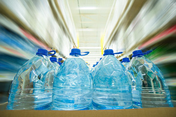 Blue bottles with water in cardboard box in supermarket. Wide an
