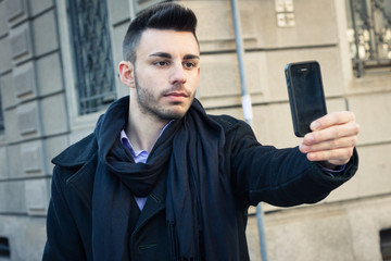 Portrait of a handsome young man taking a selfie