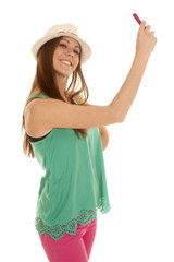 woman green tank hat phone take picture of self