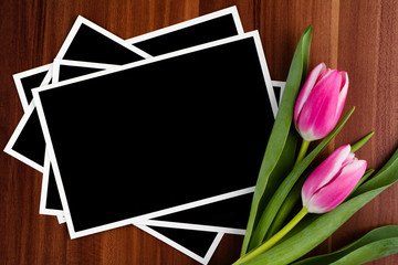Blank photos and tulips on a wooden background