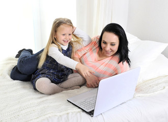 happy young mother and little daughter with computer