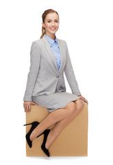 smiling woman sitting on cardboard box