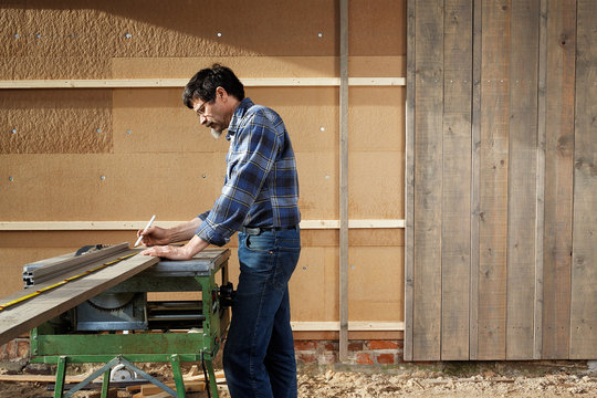 Builder at the circular saw in front of a thermal insulation