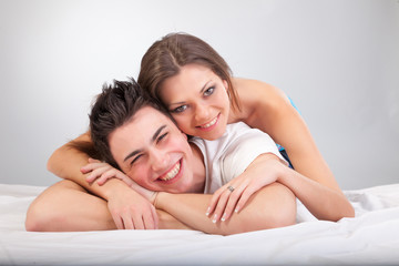 Portrait of happy young couple lying in bed and smiling