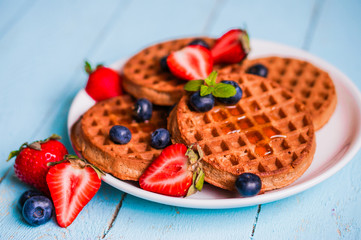 Whole grain waffles with berries on blue wooden background