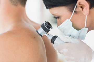 Dermatologist examining mole on patient