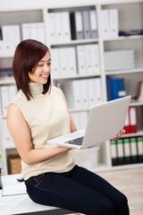 mitarbeiterin mit laptop im büro
