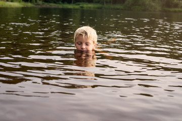 Boy swimming in a lake late afternoon