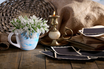 Composition with beautiful snowdrops in vase, candle, old