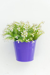 Plastic flower in vase on wall background