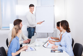 Businessman With Flipchart And Colleagues
