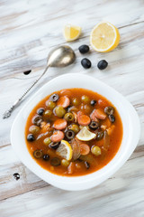 Russian traditional soup solyanka, wooden background, above view