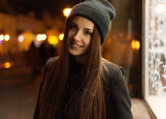 Beautiful girl smiling in the evening in the hat and coat