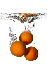 Fresh and Health Oranges Falling into Clean Water Isolated
