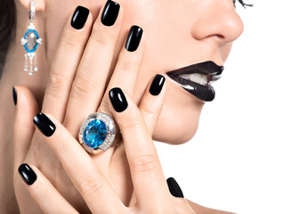 Closeup face of young beautiful woman with black manicure