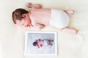 Newborn baby next to her photo on a tablet pc
