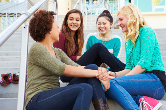 Female High School Students Sitting Outside Building
