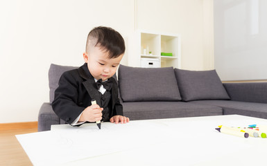 Asian little boy drawing picture at home
