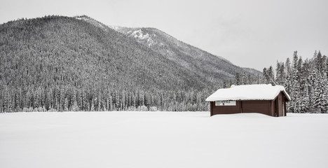 Fototapete - Lone Building Covered in Snow and Mountains