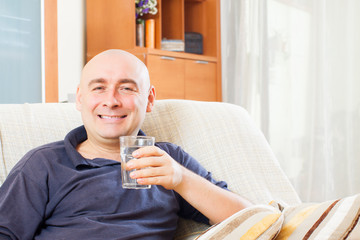 adult man sitting with glass of water