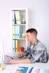 Young creative designer working at office