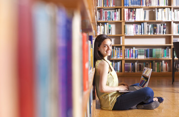 Young smiling student using her laptop in a library