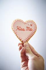 Hand holds pastry with white cream heart