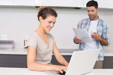 Pretty woman using laptop while partner reads the newspaper