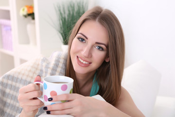 Young woman resting with cup of hot drink on sofa at home