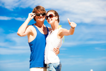 happy young couple in sunglasses smiling pointing to the sky