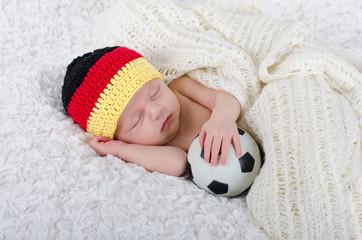 Fototapeta Newborn mit Deutschlandmütze und Fußball