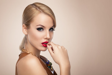 Beautiful blonde with red lipstick posing in the studio