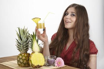 Junge Frau mit einem Glas Ananassaft und Ananas am Esstisch