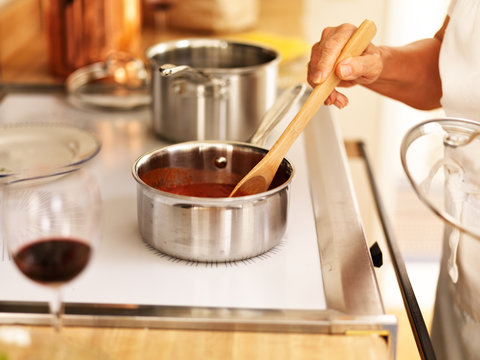 stirring a small pot of spaghetti sauce on the stove