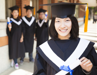pretty  female college graduate holding diploma with classmates