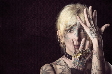 lady in dark , with tattoo onface with mask