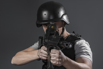 Security, paintball sport player wearing protective helmet aimin