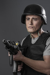 Safety, paintball sport player wearing protective helmet aiming
