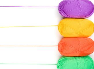 stack of yarn skeins in yellow, orange, green, purple colors on