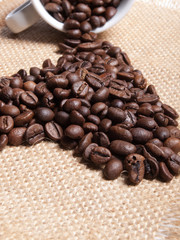 white cup with coffee beans on burlap background.