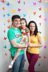 Close-up of a happy family smiling and posing in playroom