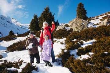 Family (mother with two children) take a walk on winter mountain