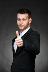 young business man in black suit with thumbs up