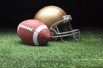 Football and helmet on grass against dark background